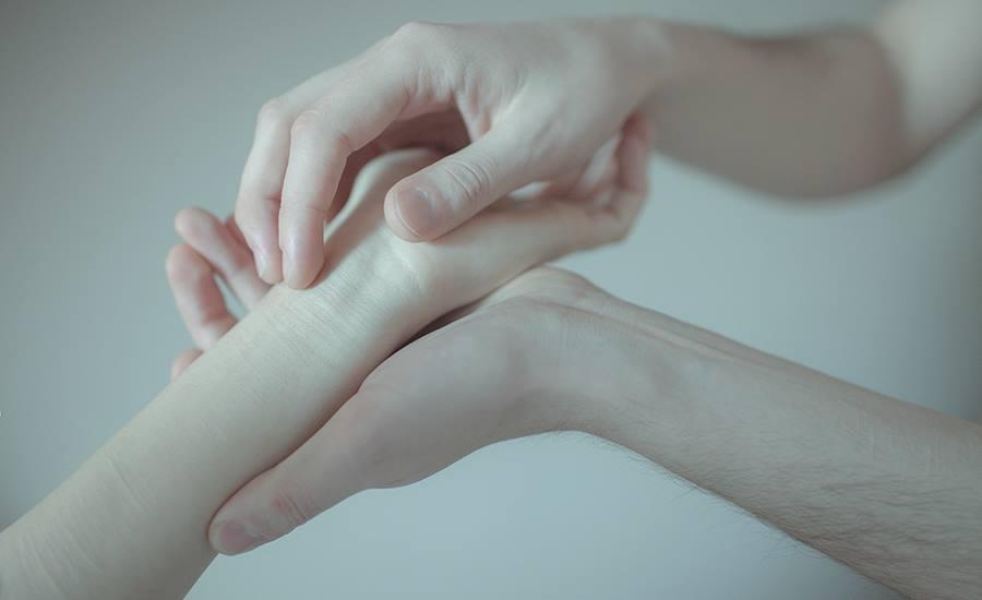 Девушка сжимает свою руку своими нога